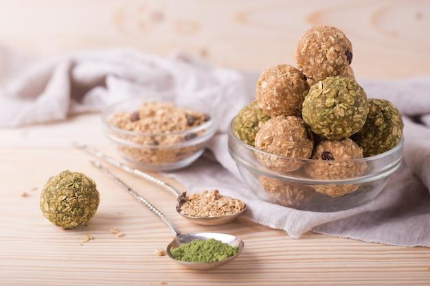 健康的な有機エネルギーのグラノーラは、ナッツ、レーズン、抹茶、ハチミツに噛まれます-ビーガンベジタリアン生スナックまたは食事 Premium写真