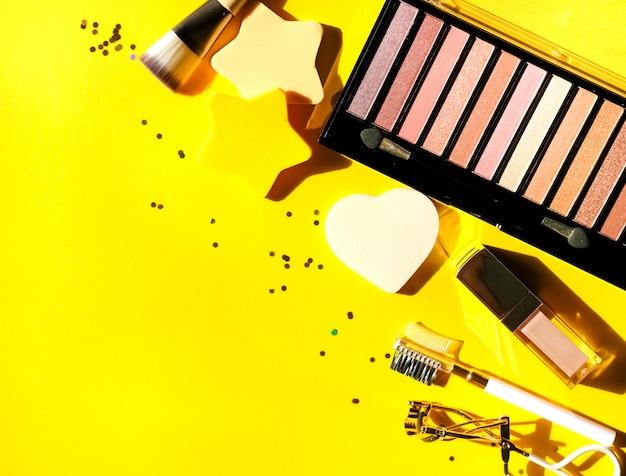各種化粧品、アイシャドウパレット、リップグロス、ブローコーム、まつげカーラー、ブラシ、黄色の背景にスポンジ。美容コンセプト。フラットレイアウトデザイン。 Premium写真