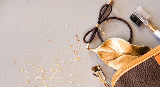 化粧品袋、まつげカーラー、光沢のあるベージュ色の背景に眉ブラシ。美容コンセプト。フラットレイアウトデザイン。 Premium写真