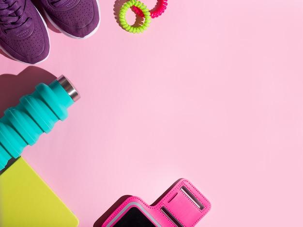 フラット横たわっていたランニングフィットネススポーツ青い水ボトル、ピンクのゴムバンド、緑の日記、電話ホルダー、ピンクの背景に紫のスニーカー Premium写真