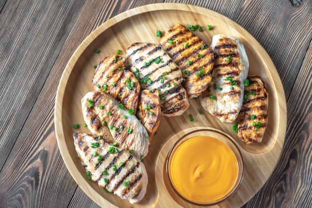 Жареная куриная грудка на деревянной доске Premium Фотографии