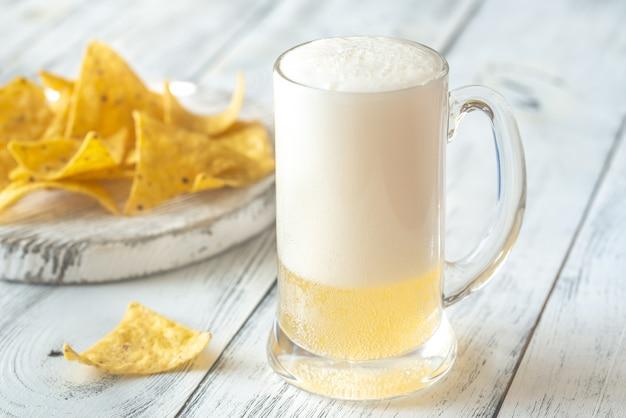 Кружка пива с чипсами из тортильи Premium Фотографии