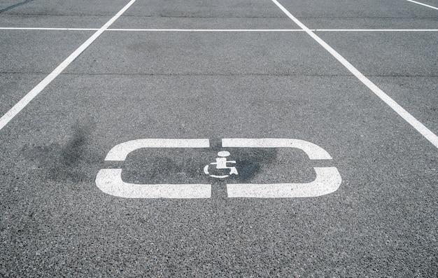 Стоянки для автомобилей, места для инвалидов, дорожный знак на асфальте. Premium Фотографии