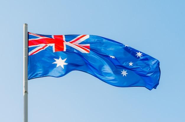 青い空にカラフルなオーストラリアの旗を振っています。 Premium写真