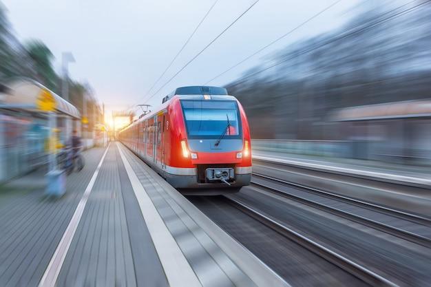 Поезд пассажира высокоскоростной красный с нерезкостью движения в станции. Premium Фотографии