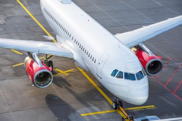 空港の太陽に照らされた、トップビューで商業飛行機の駐車場。 Premium写真
