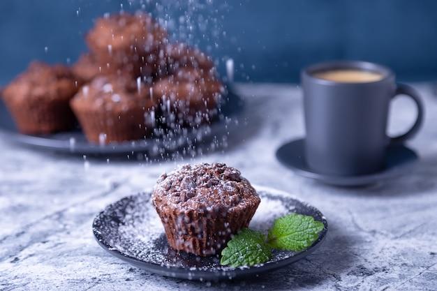 粉砂糖をまき散らした黒いプレートにミントのチョコレートマフィン。自家製のベーキング。背景には一杯のコーヒーとマフィンのプレートがあります。大理石のテーブルと青い背景。 Premium写真
