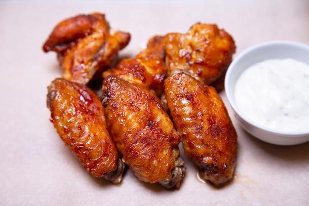 Барбекю куриные крылышки с соусом на бумаге. крупным планом, селективный фокус. Premium Фотографии