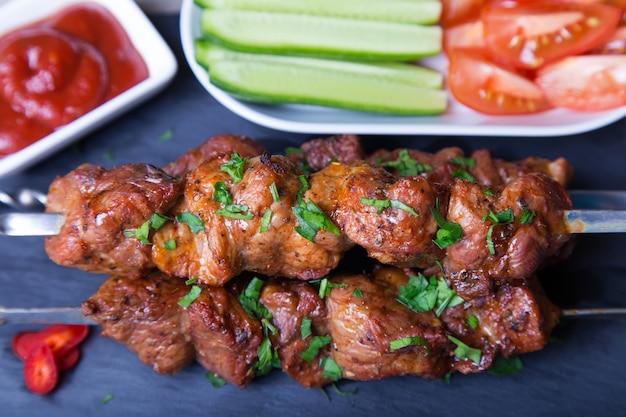 Шашлык (шашлык) из мяса (свинины) на шпажках с овощами и кетчупом. крупным планом, селективный фокус. Premium Фотографии