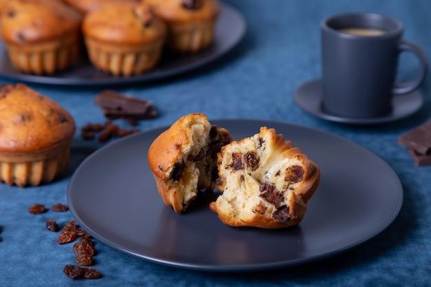 チョコレートとレーズンのマフィン。自家製のベーキング。マフィンと一杯のコーヒーのプレート。 Premium写真