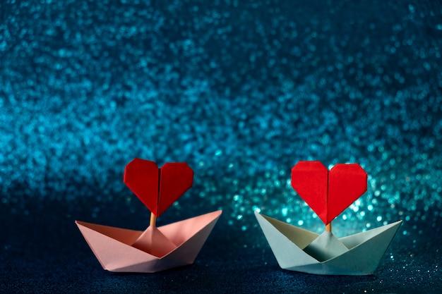 キラキラブルーの背景にピンクとブルーの紙の船。テキストのためのスペースを持つロマンチックなバレンタインデーのコンセプトです。 Premium写真