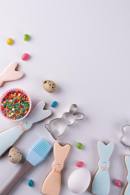 Приготовление пряников. пасхальное печенье в форме забавного кролика, инструменты, необходимые для приготовления пряничного теста, разноцветные посыпки. пасхальная концепция. Premium Фотографии