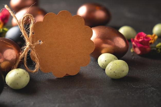 イースターエッグと空白の茶色のタグ。ハッピーイースターのグリーティングカード Premium写真