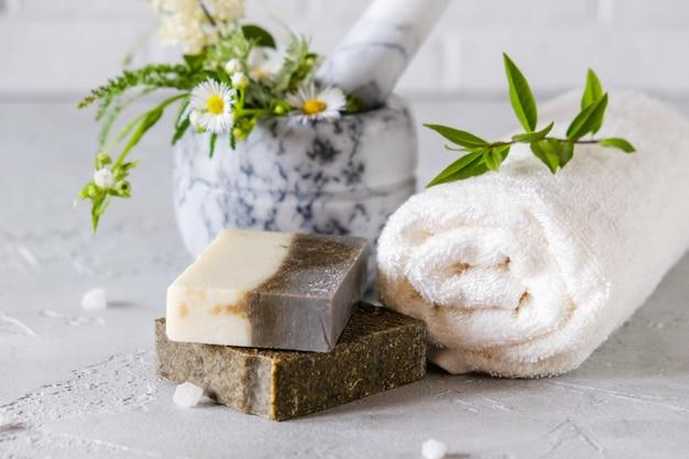 健康的なスキンケア。スパのコンセプト。乾燥ハーブと花、海の塩を使った天然の手作り石鹸。天然ハーブ製品。 Premium写真