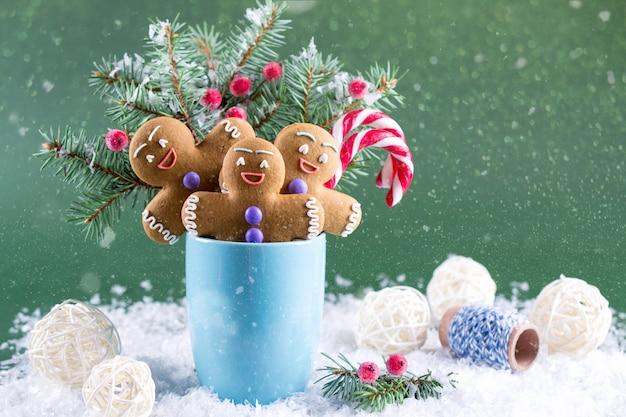 クリスマスや年賀状。モミの木、キャンディー、ジンジャーメンクッキーのカップ。 Premium写真