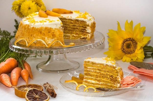 キャロットケーキの日。黄色の花とニンジンとオレンジの皮で飾られた白い表面の多層キャロットケーキ。側面図。自家製ケーキ Premium写真