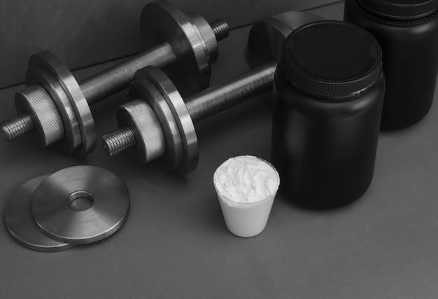 灰色の表面にダンベルでスポーツ栄養 Premium写真
