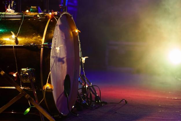 Барабанная установка на сцене басового барабана крупным планом в тумане и разноцветном освещении Premium Фотографии