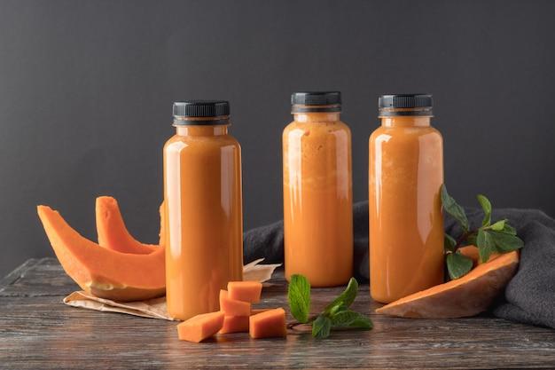 Бутылки с вкусным тыквенным смузи на деревянном столе Premium Фотографии