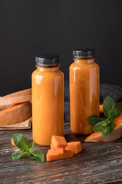 木製のテーブルにおいしいカボチャのスムージーのボトル Premium写真