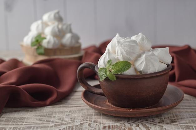Глиняная чашка с ванильным поцелуями на белом деревянном столе Premium Фотографии