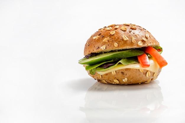 チーズと野菜の背景を持つ健康的なベジタリアンハンバーガー Premium写真