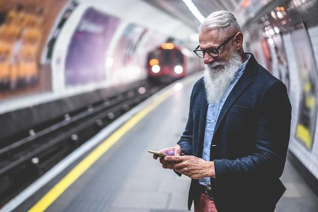 Старший хипстерский человек, использующий смартфон в подземном метро - мода зрелого человека, весело проводящего время с технологическими тенденциями, ожидающими его поезда - радостная концепция образа жизни пожилых людей - основное внимание на лице Premium Фотографии