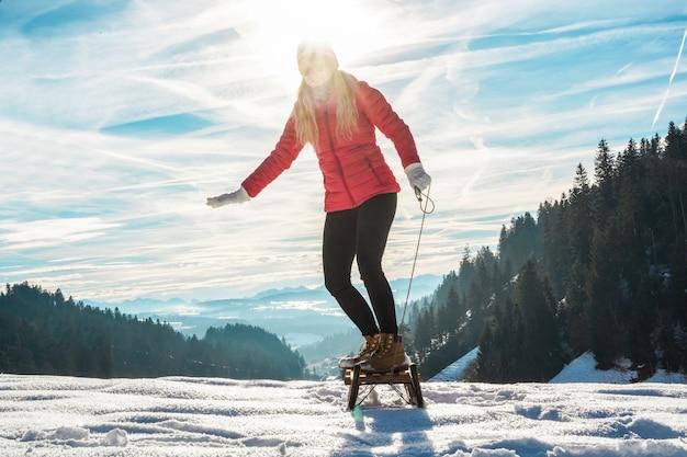 Молодая женщина несется на старинных санках по высокой снежной горе - счастливая девушка веселится в белых неделях отпуска - путешествия, зимний спорт, концепция праздника - основное внимание на ее ногах Premium Фотографии