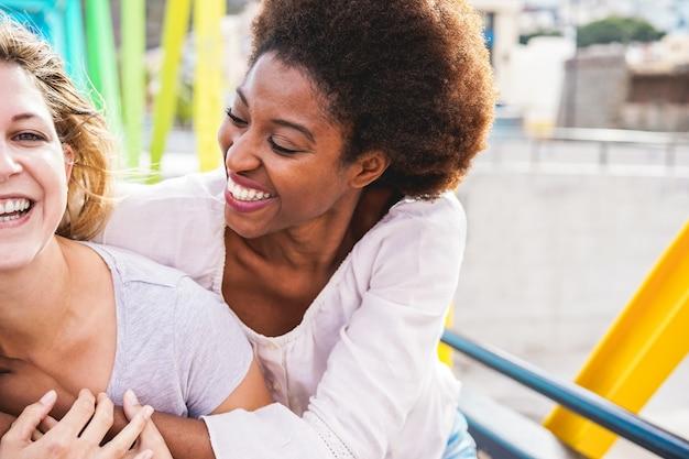 カラフルな橋の上を歩いて笑って幸せな女性の友人 Premium写真