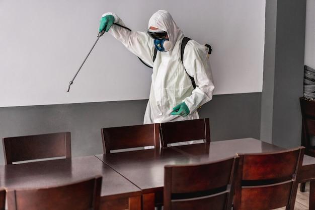 Рабочий в защитном костюме в защитной маске при дезинфекции в баре-ресторане Premium Фотографии