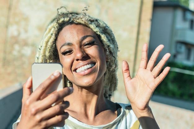 スマートな携帯電話でビデオ通話を行う金髪のドレッドヘアを持つ若いアフリカ人女性 Premium写真