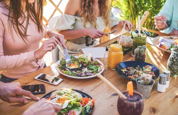 ブランチを食べたり、トレンディなバーレストランで生態学的なストローでスムージーボウルを飲む若者の手のビュー。健康的なライフスタイル、食品トレンドコンセプト Premium写真