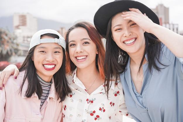 屋外楽しんでアジアの女性の友人。一緒に笑って幸せなトレンディな女の子 Premium写真
