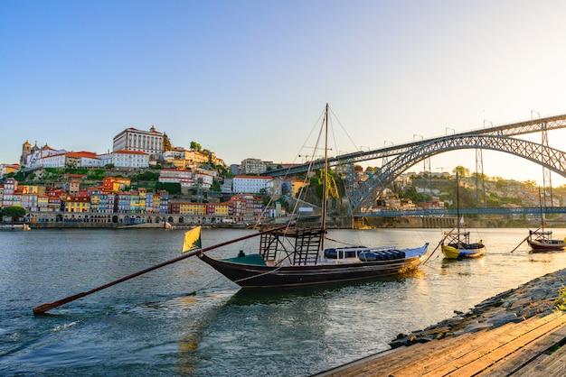 Порту, португалия городской пейзаж старого города на реке дору с традиционными лодками рабело с бочками с вином и мостом Premium Фотографии