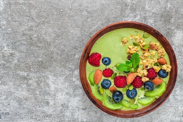Чаша из зеленого чая матча со свежими ягодами, фруктами, мюсли, орехами и семечками для здорового веганского завтрака Premium Фотографии