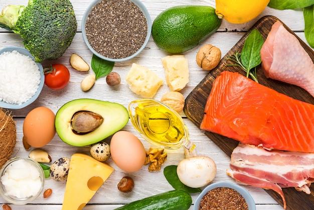 ケトダイエットコンセプト。ケトジェニックダイエット食品。バランスの取れた低炭水化物食品。野菜、魚、肉、チーズ、ナッツ、種子 Premium写真