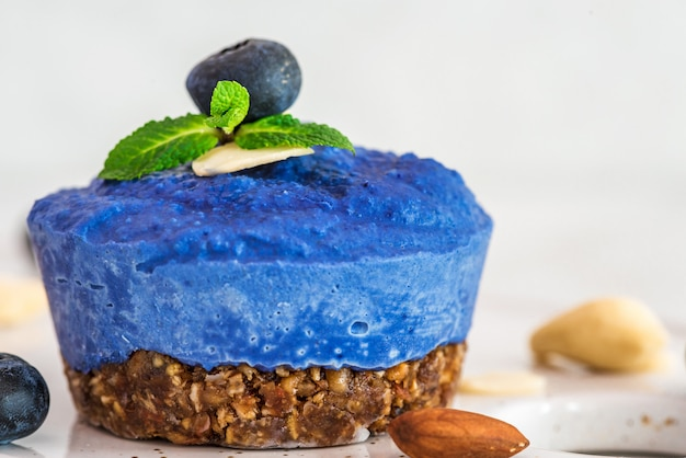 Сырой черничный, асаи и бабочка гороховый цветок веганский торт со свежими ягодами, мятой, орехами. концепция здорового веганского питания Premium Фотографии