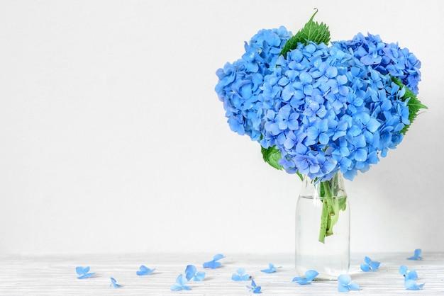 水滴のある青いアジサイの花の美しい花束のある静物。 Premium写真