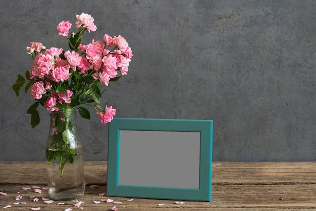 ピンクのバラの花、空白のフォトフレーム、花びらの花束のある静物 Premium写真