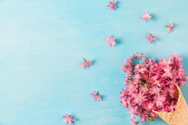 Весенние розовые вишни цветущие цветы в вафельном конусе. плоская планировка вид сверху с копией пространства Premium Фотографии