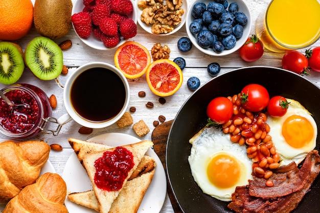 Завтрак, включающий кофе, жареные яйца, бекон, бобы, тосты, круассаны, апельсиновый сок с фруктами и ягодами. Premium Фотографии
