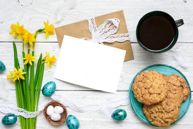 イースターエッグ、春の花、コーヒーと朝食のクッキーとイースターのグリーティングカード Premium写真