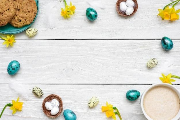 イースターエッグ、カップのカプチーノ、春の花、白い木製のテーブルのビスケットで作られたフレーム。イースター組成 Premium写真