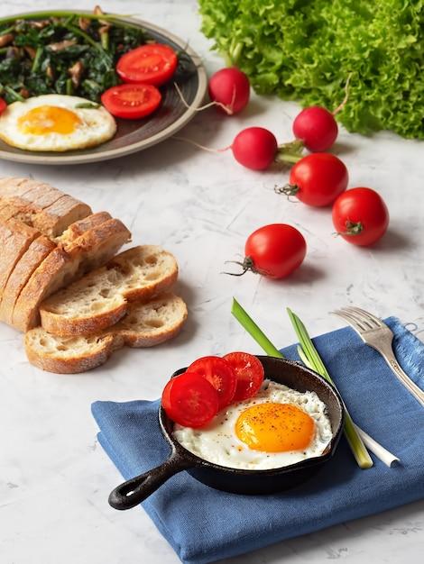 Вкусные жареные яйца в сковороде с жареным шпинатом и грибами, расположенный на сером столе. крупный план. Premium Фотографии