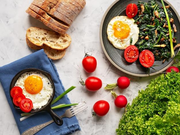 Вкусные жареные яйца на тарелку и в небольшой кастрюле с жареным шпинатом и грибами, расположенный на сером столе. вид сверху. Premium Фотографии
