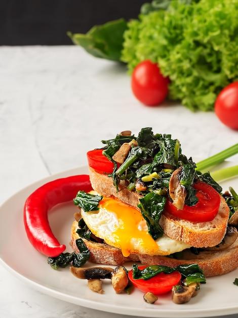 Тост с яичницей на поджаренном хлебе со шпинатом, грибами и помидорами на серой тарелке. крупный план. жареное яйцо на завтрак. Premium Фотографии