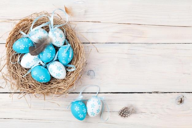 Пасхальный фон с синими и белыми яйцами в гнезде Premium Фотографии