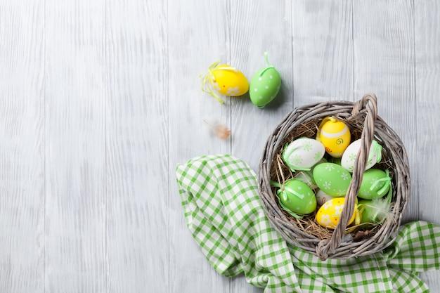 Красочные пасхальные яйца в корзине Premium Фотографии