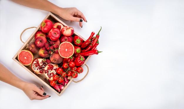 女の子は、灰色の背景に新鮮な赤い野菜や果物の木製トレイを保持しています。健康的な食事のベジタリアンコンセプト。 Premium写真