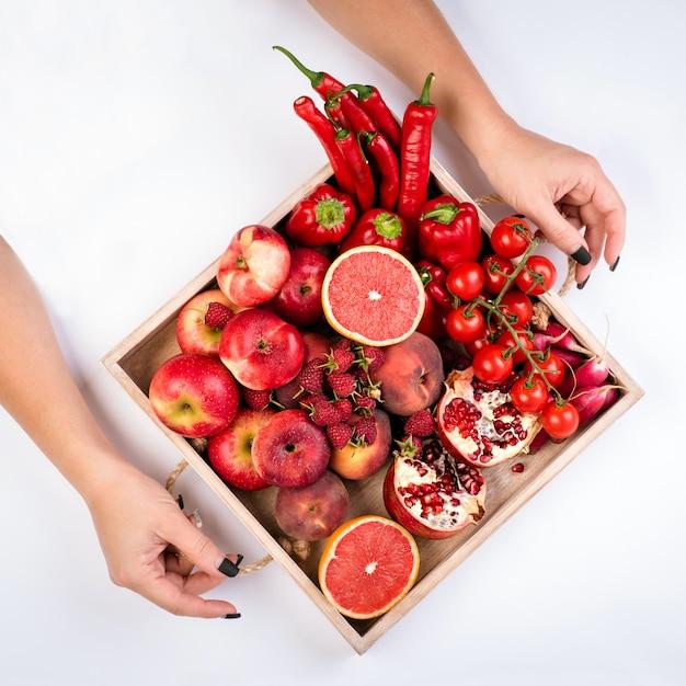 女の子は、白い背景の上に新鮮な赤い野菜や果物の木製トレイを保持しています。健康的な食事のベジタリアンコンセプト。 Premium写真